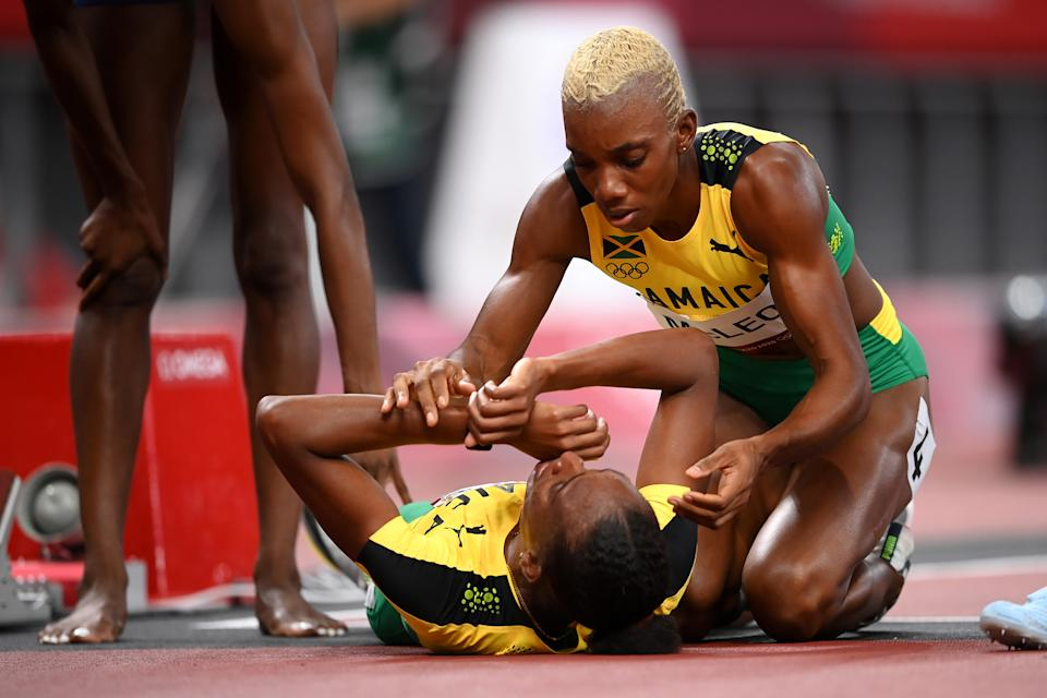 <p>Candice McLeod of Team Jamaica assists the injured Stephenie Ann McPherson of Team Jamaica following the Women's 400 metres final on day fourteen of the Tokyo 2020 Olympic Games at Olympic Stadium on August 06, 2021 in Tokyo, Japan. (Photo by Matthias Hangst/Getty Images)</p>
