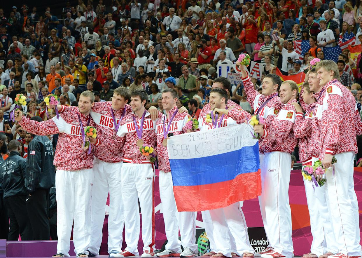 Russian players pose on the podium after winning the bronze medal in the London 2012 Olympic Games men's basketball competition at the North Greenwich Arena in London on August 12, 2012. The US won the gold medal followed by the silver to Spain and the bronze to Russia. AFP PHOTO /MARK RALSTON        (Photo credit should read MARK RALSTON/AFP/GettyImages)