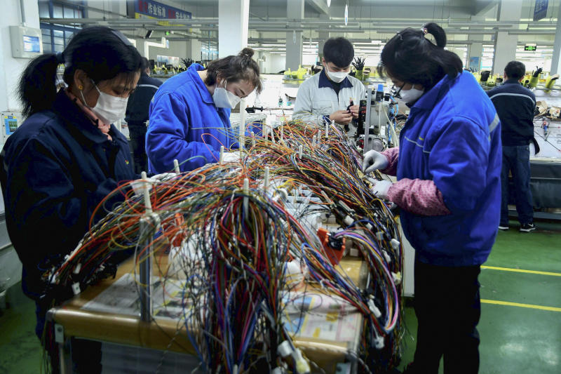 In this Feb. 13, 2020, photo, masked workers assemble wiring for automobile at a factory in Qingdao in east China's Shandong province. Automakers are gradually reopening factories in China that were idled by anti-virus controls as they try to reverse a sales slump in their biggest market. (Chinatopix via AP)