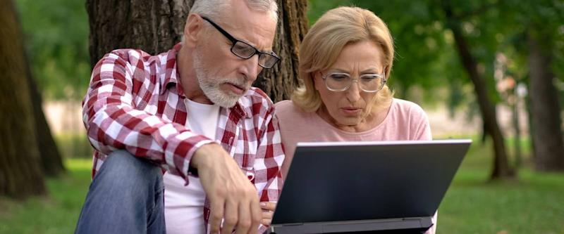 Old man and woman sitting on grass and watching thriller movie trailer on laptop