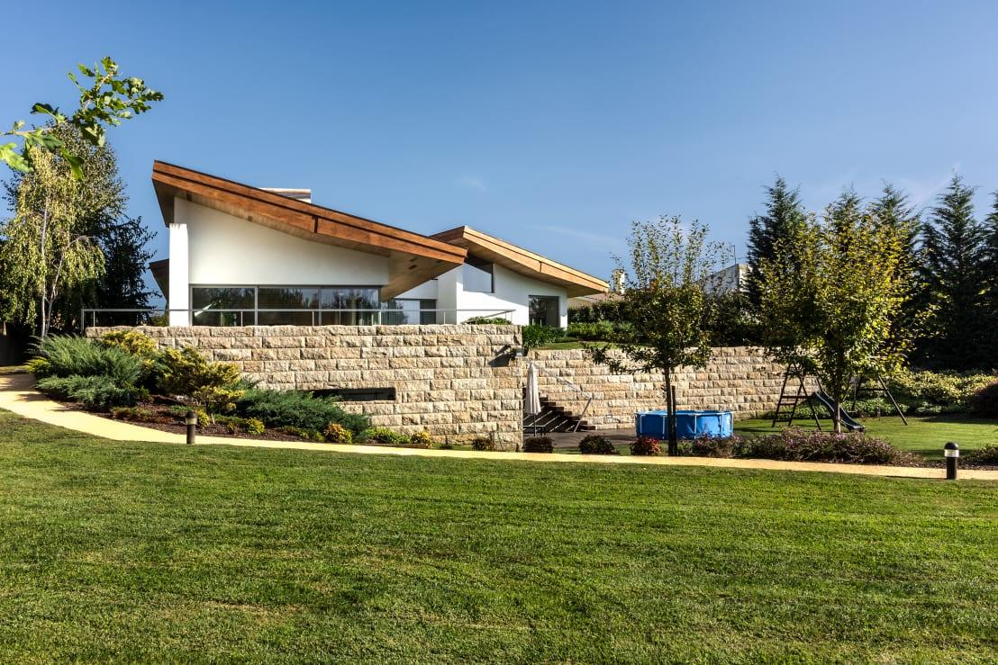 """<p>Even from the outside we can already catch a glimpse of the wooden roof, which expertly contrasts with the stone wall and lush garden trimmings.</p><p>Need that expert interior (or exterior) look? Check out our range of<a rel=""""nofollow"""" href=""""https://www.homify.co.uk/professionals"""">professionals</a>.</p>  Credits: homify / João Boullosa"""