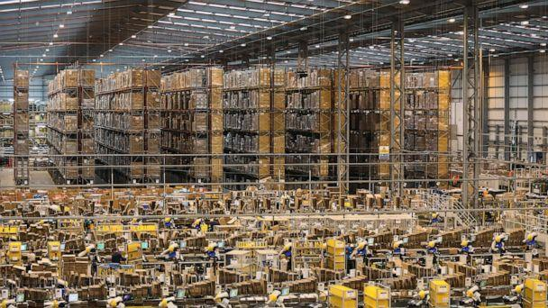 PHOTO: Storage racks stand beyond employees as they process customer orders at one of Amazon.com Inc.'s fulfillment centers in Peterborough, U.K., Nov. 25, 2014. (Chris Ratcliffe/Bloomberg/Getty Images)