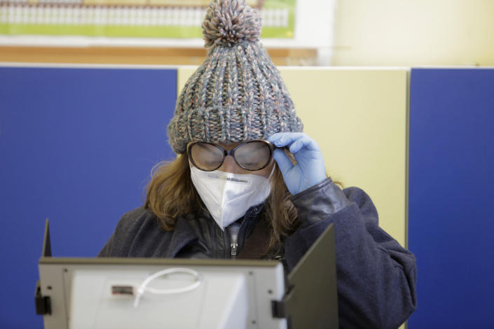 A woman with fogged glasses casts her vote using a machine in Sofia, Bulgaria, Sunday, April 4, 2021. Bulgarians are heading to the polls on Sunday to cast ballots for a new parliament after months of anti-government protests and amid a surge of coronavirus infections. (AP Photo/Valentina Petrova)