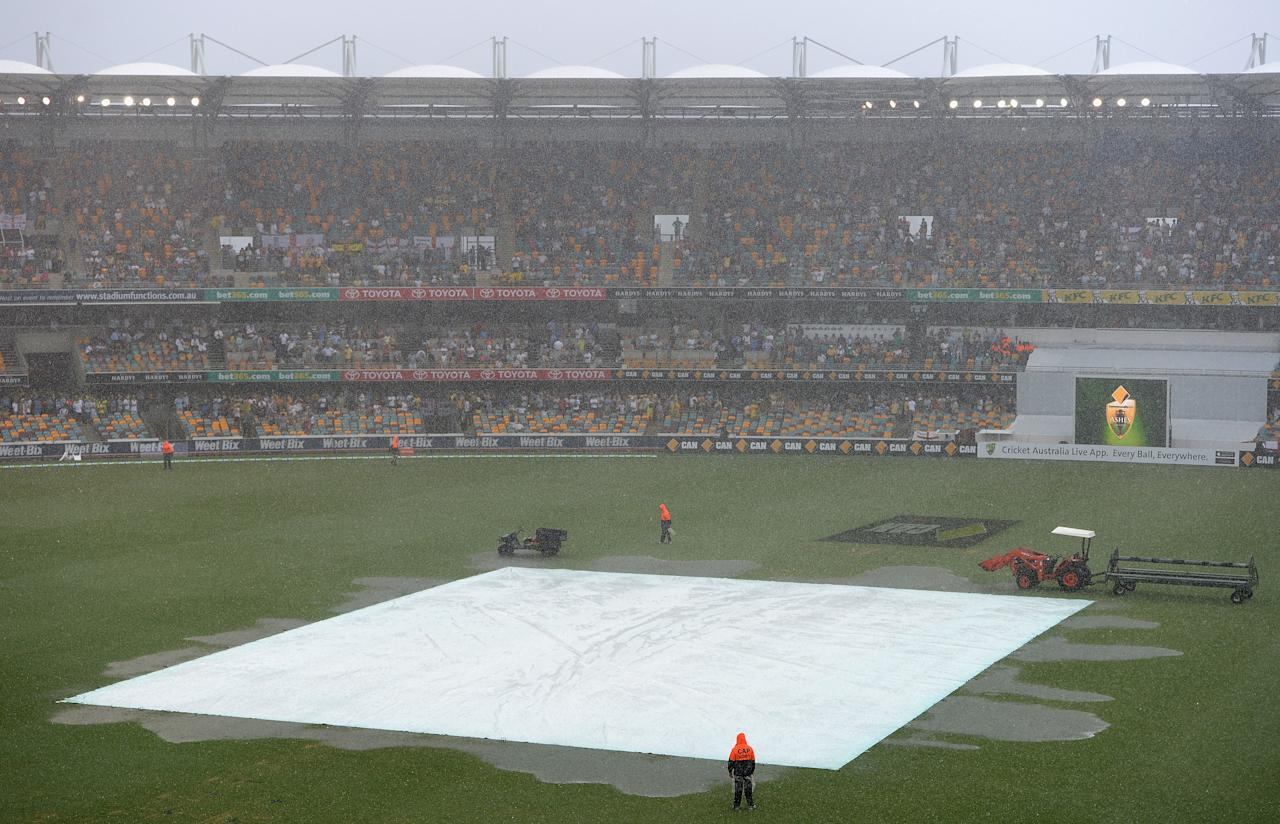 BRISBANE, AUSTRALIA - NOVEMBER 24:  The cover protect the wicket as rain stops play during day four of the First Ashes Test match between Australia and England at The Gabba on November 24, 2013 in Brisbane, Australia.  (Photo by Gareth Copley/Getty Images)