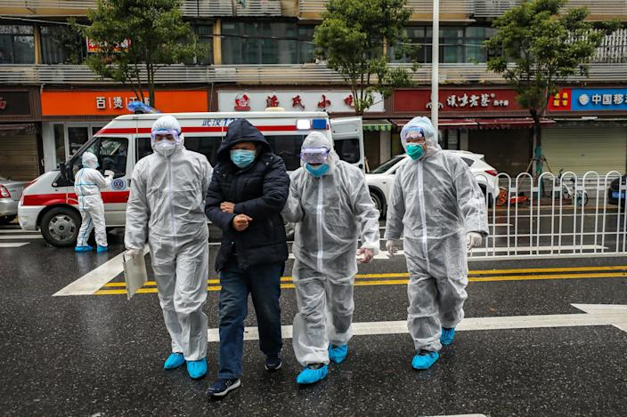 Medics help a patient walk into a hospital in Wuhan on January 26, 2020.