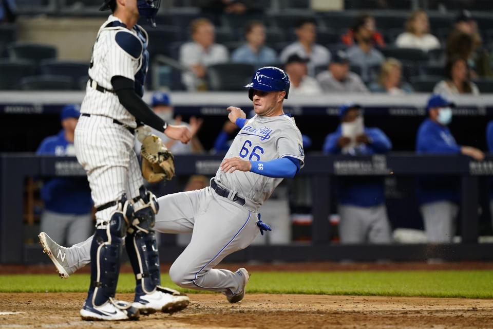 Kansas City Royals designated hitter Ryan O'Hearn (66) scores ahead of the throw to New York Yankees catcher Kyle Higashioka on Michael Taylor's RBI single during the eighth inning of a baseball game, Tuesday, June 22, 2021, at Yankee Stadium in New York. (AP Photo/Kathy Willens)