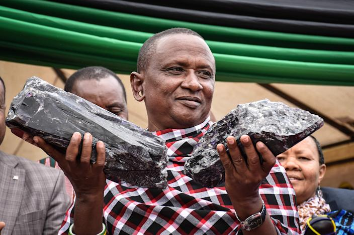 Tanzanian small-scale miner Saniniu Kuryan Laizer, 52, poses with two of the biggest of the country's precious gemstones, Tanzanite, as a millionaire during the ceremony for his historical discovery in Manyara, northern Tanzania, on June 24, 2020.