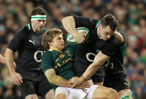 Ireland's prop Cian Healy (R) is tackled by South Africa's fly half Pat Lambie (2nd L)
