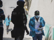 A forensic investigator carries a bagful of bullet casings collected at the residence of Haiti's President Jovenel Moise, near the leader's residence where he was killed by gunmen in the early morning hours, in Port-au-Prince, Haiti, Wednesday, July 7, 2021. (AP Photo/Joseph Odelyn)