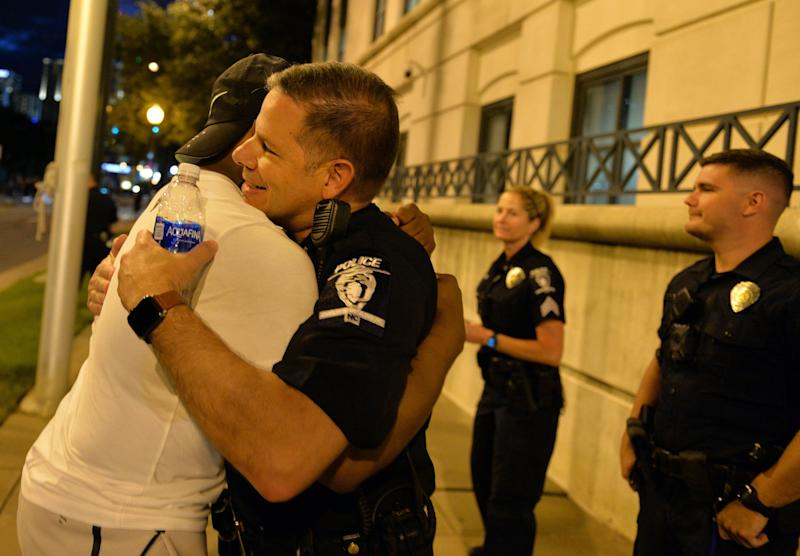 A demonstrator and a police officer hug in Charlotte, N.C. on May 30, 2020.