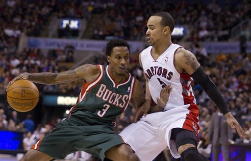 Milwaukee Buck Brandon Jennings tries to get past Toronto Raptor Jerryd Bayless during first half NBA play in Toronto on Sunday, March 11, 2012. (AP Photo/The Canadian Press, Pawel Dwulit)