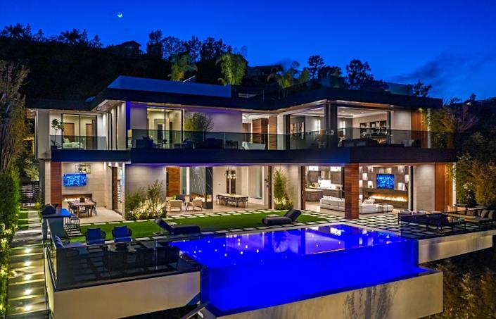 "Accent lighting and modern fixtures enhance the visual allure of this newly built home in Brentwood. Listed for $12.899 million, the six-bedroom, nine-bathroom residence was built by Huntington Estate Properties and sits on about a third of an acre with an infinity-edge swimming pool. High ceilings, marble slabs and a floating glass-and-steel staircase are among features of the 9,300-square-foot showplace. An illuminated waterfall feature and a two-way fireplace bookend the dining room. Other amenities include a movie theater, a wine room and a gym. Atop the house, a rooftop deck takes in tree-top and canyon views. <span class=""copyright"">(Berlyn Photography/Berlyn Photography)</span>"