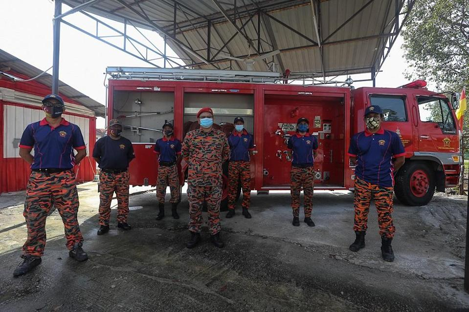Members of the Pasukan Bomba Sukarela Saujana Utama (PBSSU) pose for a photograph in front of their station. — Picture by Mohd Yusof Mat Isa