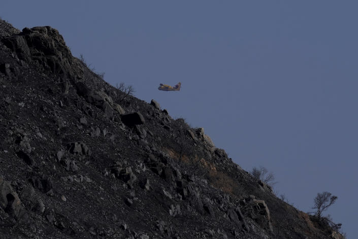 """A canadair flies over the burned Larnaca mountain region near Ora village, Cyprus, Sunday, July 4, 2021. Cyprus' interior minister says four people have died in what he called the """"most destructive"""" fire in the island nation's history. (AP Photo/Petros Karadjias)"""