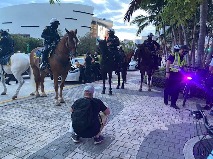 Police on horseback in front of a person being arrested in Miami.