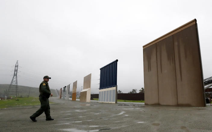 FILE - In this Feb. 5, 2019, file photo, a Border Patrol agent walks towards prototypes for a border wall in San Diego. The prototypes were taken down in February. (AP Photo/Gregory Bull, File)