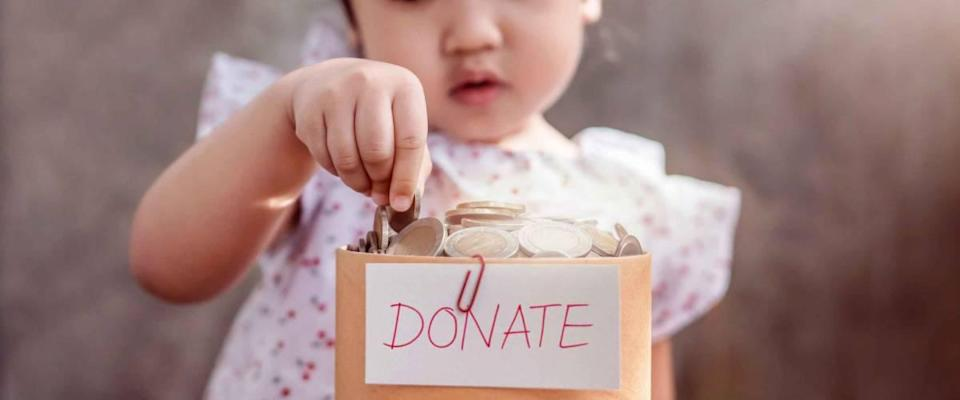 Children with Donation Concept. 2 Years Old Child putting Money Coin into a Donate Box