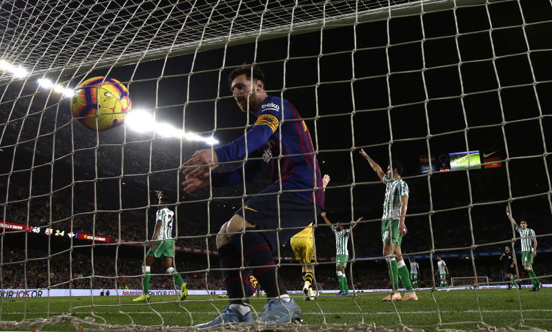 FC Barcelona's Lionel Messi collects a ball from the net after scoring a penalty during the Spanish La Liga soccer match between FC Barcelona and Betis at the Camp Nou stadium in Barcelona, Spain, Sunday, Nov. 11, 2018. (AP Photo/Manu Fernandez)