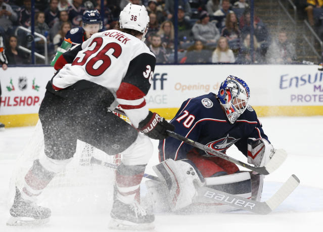 Columbus Blue Jackets' Joonas Korpisalo, right, of Finland, makes a save against Arizona Coyotes' Christian Fischer during the first period of an NHL hockey game Tuesday, Dec. 3, 2019, in Columbus, Ohio. (AP Photo/Jay LaPrete)