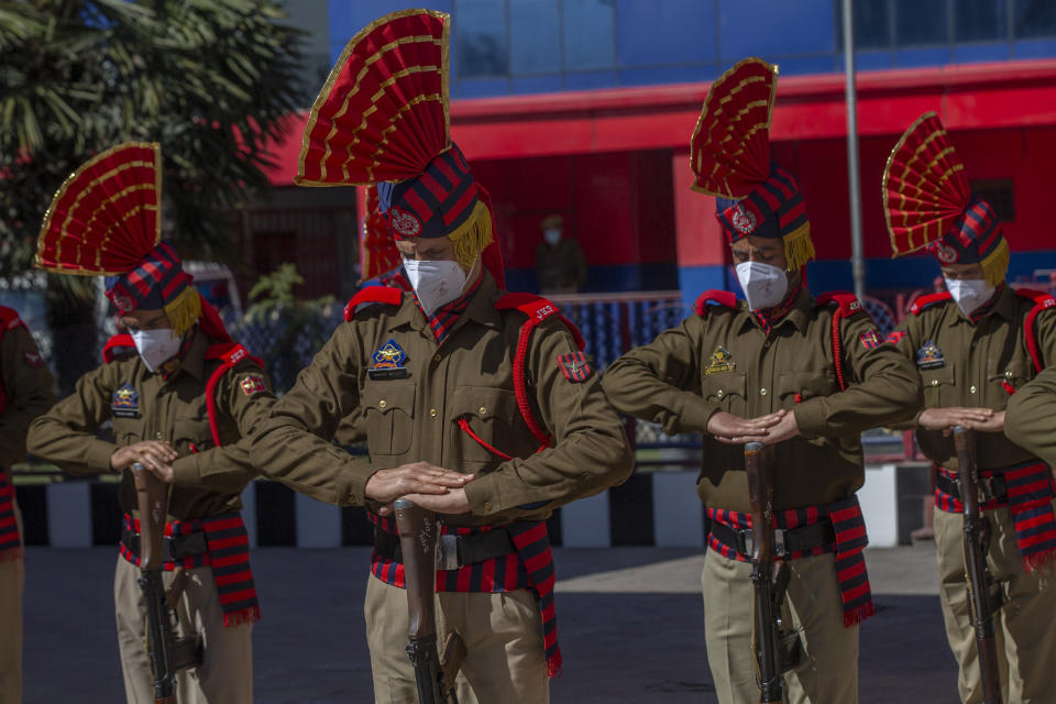 Indian police officers salute as they pay respect to their colleague Rameez Ahmad during a wreath laying ceremony in Srinagar, Indian controlled Kashmir, Thursday, April 1, 2021. Gunmen in disputed Kashmir on Thursday killed a policeman as they tried to storm the residence of a politician of India's ruling party, police said. (AP Photo/ Dar Yasin)