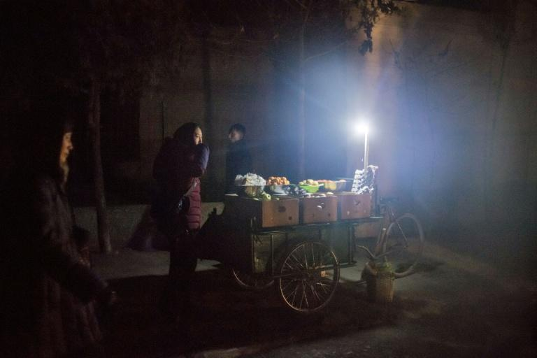 A fruit vendor waits for customers in an alleyway in Pyongyang, North Korea