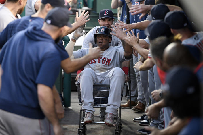 Boston Red Sox' Rafael Devers, front, celebrates his two-run home run in the dugout during the ninth inning of a baseball game against the Washington Nationals, Sunday, Oct. 3, 2021, in Washington. The Red Sox won 7-5. (AP Photo/Nick Wass)