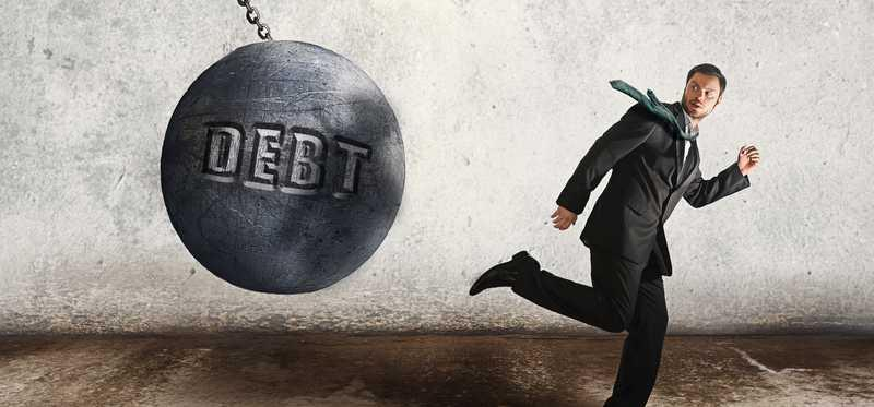 The word debt on a wrecking ball swinging towards a man running away.