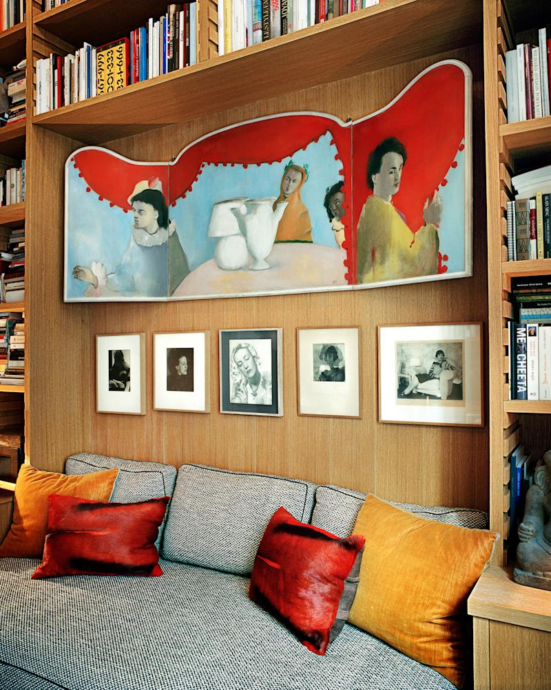 In the library, a banquette is tucked beneath an oak bookcase. Christian Bérard triptych; Man Ray photographs.