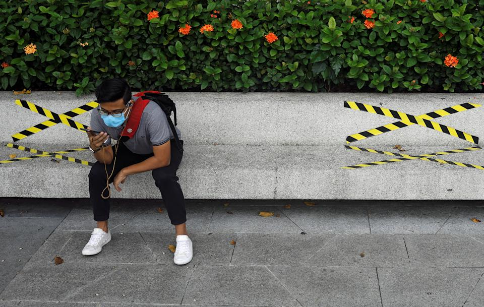 A man sits on a bench with distance markers along Marina Bay, amid the coronavirus disease (COVID-19) outbreak, in Singapore July 14, 2020. REUTERS/Edgar Su