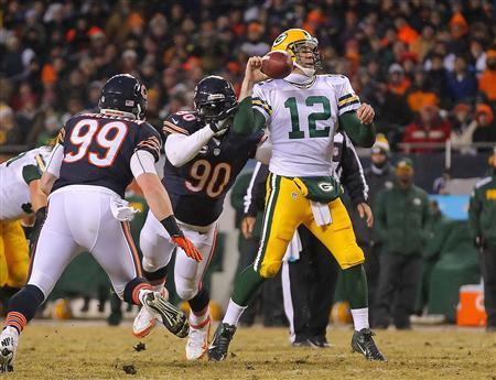 Dec 29, 2013; Chicago, IL, USA; Chicago Bears defensive end Julius Peppers (90) hits Green Bay Packers quarterback Aaron Rodgers (12) and causes a fumble during the second quarter at Soldier Field. Mandatory Credit: Dennis Wierzbicki-USA TODAY Sports