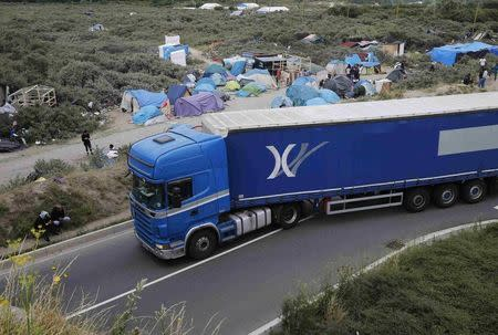 A lorry drives past a field with tents and makeshift shelters where migrants and asylum seekers stay in Calais, northern France, July 30, 2015. REUTERS/Pascal Rossignol
