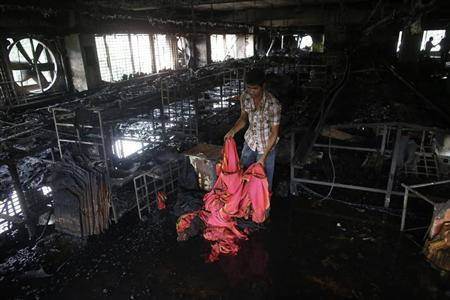 A garment worker inspects a factory belonging to Tung Hai Group, a large garment exporter, after a fire in Dhaka.
