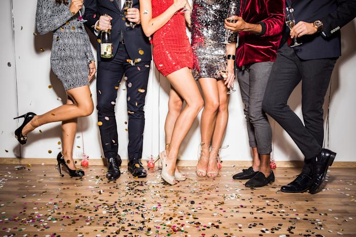 Multi ethnic group of friends enjoy in new years party celebration. Only legs visible