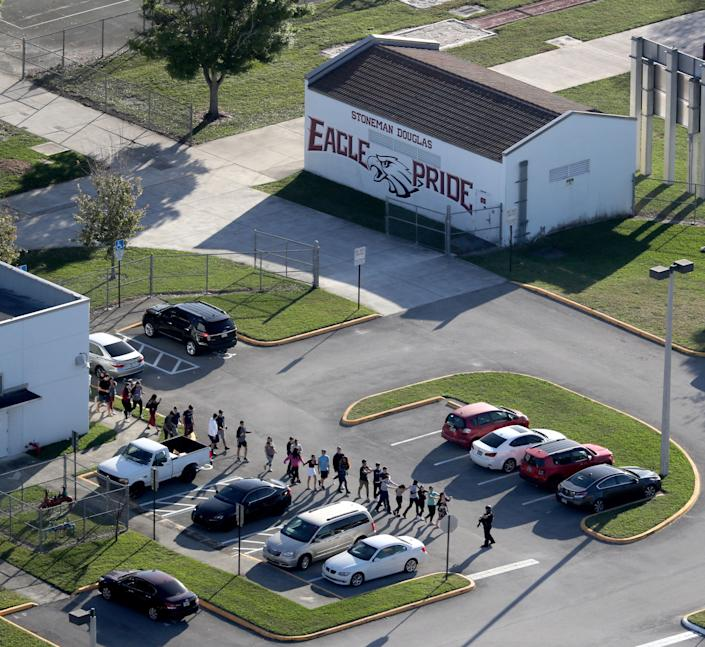 Students are evacuated by police out of Stoneman Douglas High School.