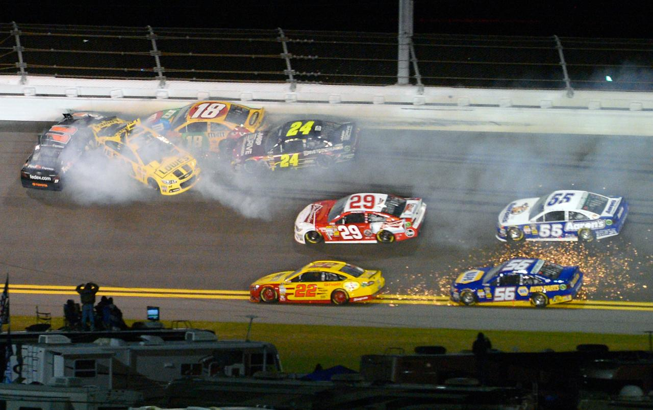 Denny Hamlin (11), Jimmie Johnson, second from left, Kyle Busch (18) and Jeff Gordon (24) collide in Turn 2 during the NASCAR Daytona Shootout auto race at Daytona International Speedway in Daytona Beach, Fla., Saturday, Feb. 16, 2013.(AP Photo/Phelan M. Ebenhack)