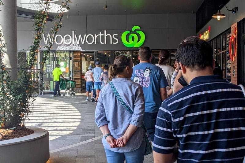 Shoppers line up outside a Woolworths store at Montague Markets West End in Brisbane.