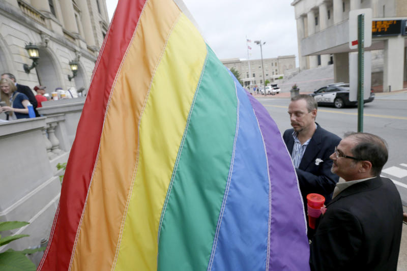 James Porter, right, and his partner Shon DeArmon carry a flag in support of the county issuing marriage licenses for same-sex couples at the Pulaski County Courthouse in Little Rock, Ark., Monday, May 12, 2014. Dozens of gay couples, some of whom waited in line overnight, received licenses to marry from county clerks Monday, while lawyers for the state of Arkansas asked its highest court to suspend an order gutting a constitutional amendment that bans same-sex marriage. (AP Photo/Danny Johnston)