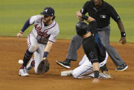 Atlanta Braves shortstop Dansby Swanson, left, attempts to tag Miami Marlins' Adam Duvall, front right, who steals second base during the ninth inning of a baseball game, Saturday, June 12, 2021, in Miami. (AP Photo/Wilfredo Lee)