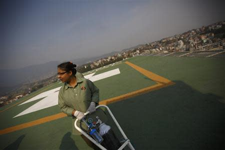 A staff member expecting the arrival of victims of a Mount Everest avalanche standbys near the helipad at Grandi International Hospital in Kathmandu April 18, 2014. REUTERS/Navesh Chitrakar