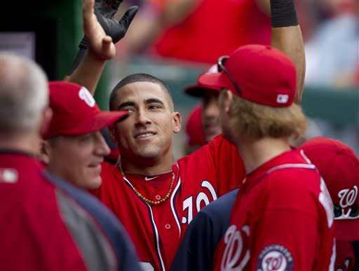 Washington Nationals shortstop Ian Desmond, center, is congratulated by teammates after hitting a home run during the sixth inning of a baseball game against the Philadelphia Phillies in Washington, Saturday, May 5, 2012. The Nationals won 7-1. (AP Photo Manuel Balce Ceneta)