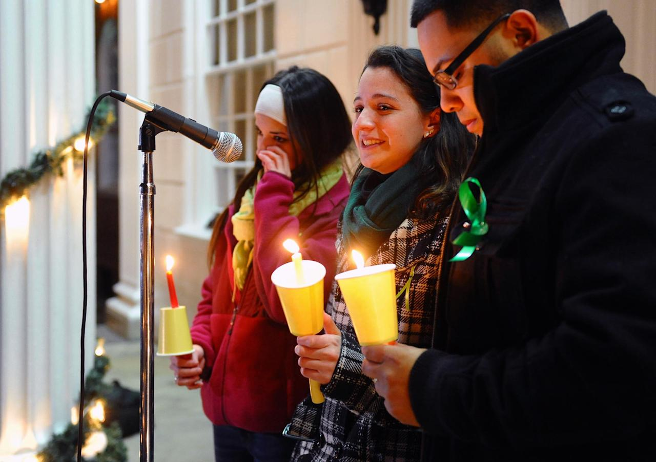 Jillian Soto, center, thanks the hundreds of people who came out to attend a candlelight vigil in memory of victims from the mass shooting in Newtown, Conn., which was held behind Stratford High School on the Town Hall Green in Stratford, Conn. on Saturday December 15, 2012. Jillian's sister Vicki, a Stratford native, was a teacher at Sandy Hook Elementary School and was one of the victims in the shooting. At left is sister Carly Soto and family friend Louis Sanchez. (AP Photo/The Connecticut Post, Christian Abraham) MANDATORY CREDIT