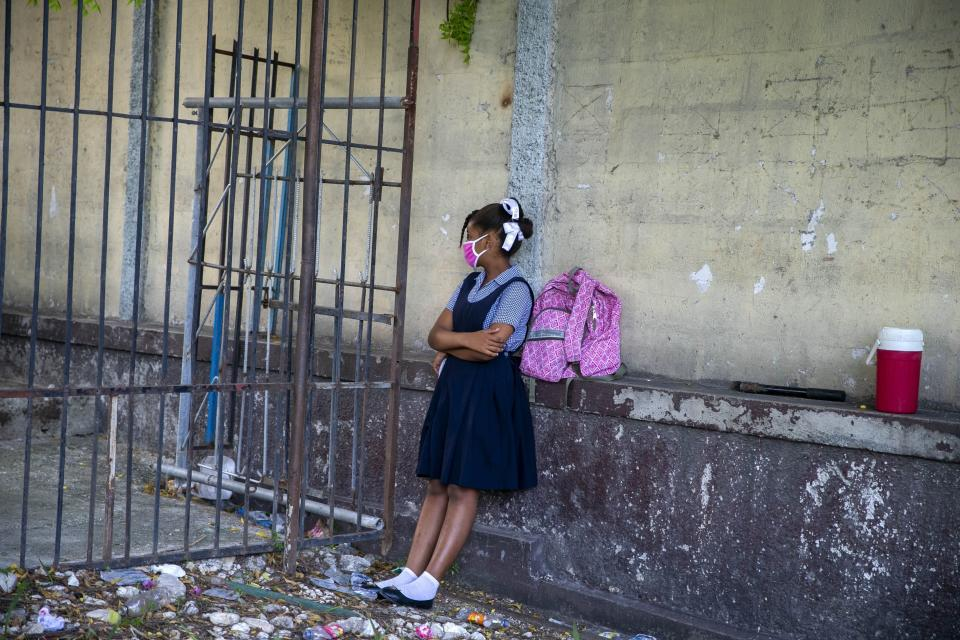 FILE - In this Aug. 17, 2020 file photo, a student waits for her turn to enter the Lycee Marie Jeanne school on the first day back to school since the COVID-19 pandemic in Port-au-Prince, Haiti. After five months of lockdown, schools officially reopened, requiring students to wear masks and dividing students into smaller groups with different schedules. (AP Photo/Dieu Nalio Chery, File)