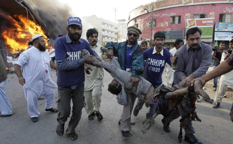 Pakistani volunteers carry a wounded bus passenger following a blast in Karachi, Pakistan on Saturday, Dec. 29, 2012. The blast that ripped through the bus  set the vehicle on fire and reduced it to little more than a charred skeleton, killing scores of people and left many injured. Police were trying to determine whether the explosion was caused by a bomb or a gas cylinder, said police spokesman. Many buses in Pakistan run on natural gas. (AP Photo/Fareed Khan)