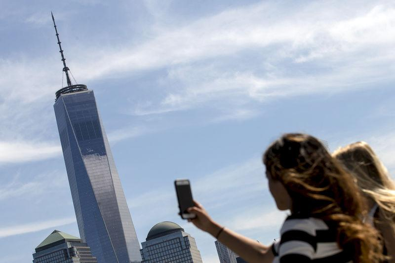 FILE PHOTO: A woman uses her phone to photograph One World Trade Center tower in New York