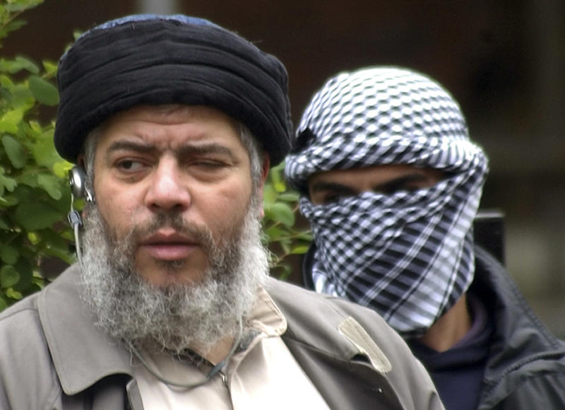 FILE - This Friday, April 30, 2004 file photo shows Muslim cleric Abu Hamza al-Masri, as he arrives with a masked bodyguard, right, to conduct Friday prayers in the street outside the closed Finsbury Park Mosque in London.  A British court is expected to rule on whether extremist cleric Abu Hamza al-Masri is too ill to be extradited to the United States to face terror charges. London's High Court is set to decide Friday Oct. 5, 2012 whether al-Masri and other terror suspects can be sent to the U.S. to face charges that include helping set up a terrorist training camp in rural Oregon. (AP Photo/Max Nash, File)