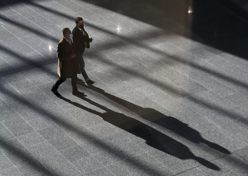 People walk inside the Agora hallway during a meeting of NATO foreign ministers at NATO headquarters in Brussels, Tuesday, March 23, 2021. (Yves Herman, Pool via AP)