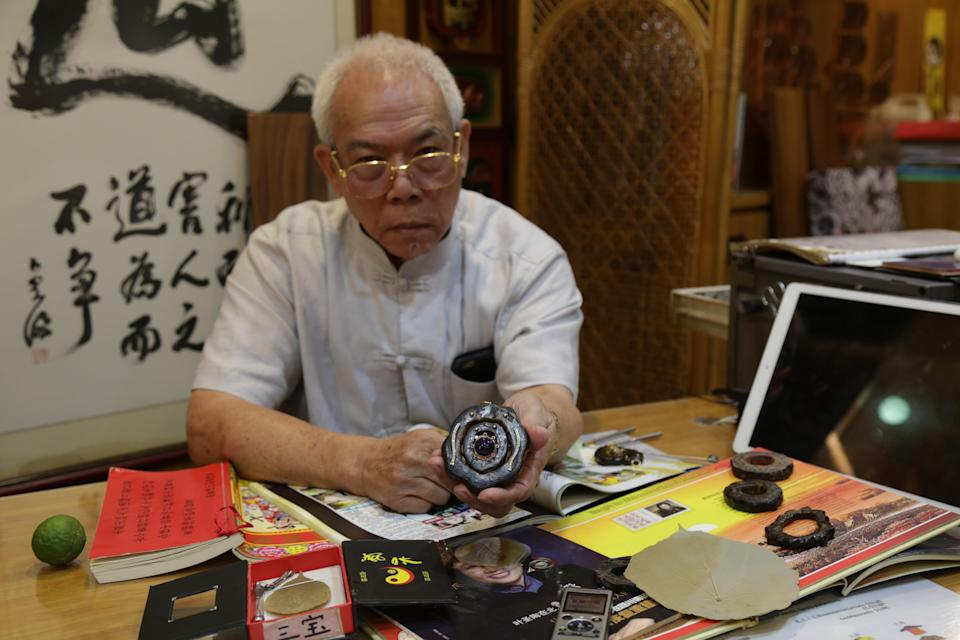 Chew holding a customised amulet that he wears every day. (PHOTO: Dhany Osman/Yahoo News Singapore)