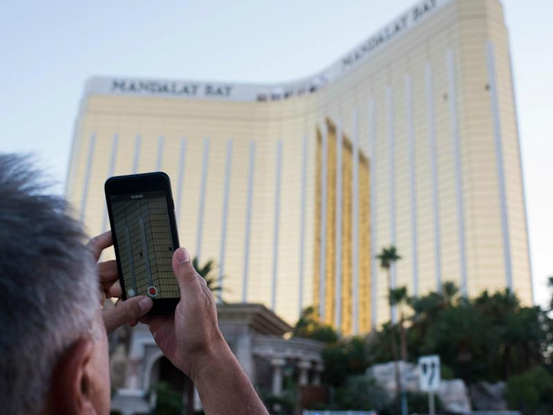 A man on the Las Vegas Strip 4 October 2017 films on his phone the two broken windows of the Mandalay Bay hotel from which killer Stephen Paddock let loose the worst mass shooting in modern American history three days prior: ROBYN BECK/AFP/Getty Images