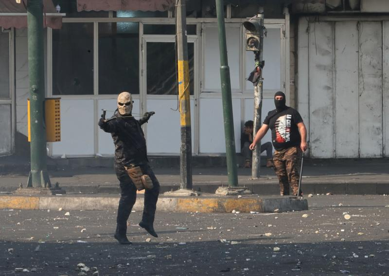A policeman uses a slingshot to fire a stone towards demonstrators during ongoing protests in downtown Baghdad, Iraq, Sunday, Nov. 10, 2019. On Sunday, Amnesty International called on Iraqi authorities to immediately rein in security forces after at least six protesters were killed in central Baghdad amid a widening security crackdown. The deaths, including five by live ammunition, occurred Saturday during a police operation to clear demonstrations from several bridges and streets near Tahrir Square, the epicenter of the protests. (AP Photo/Khalid Mohammed)