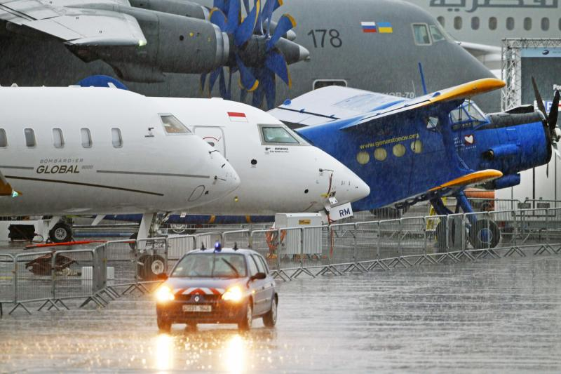 A police vehicle patrols under the rain during the first day of the Paris Air Show at Le Bourget airport, north of Paris, Monday June 17, 2013. (AP Photo/Remy de la Mauviniere)